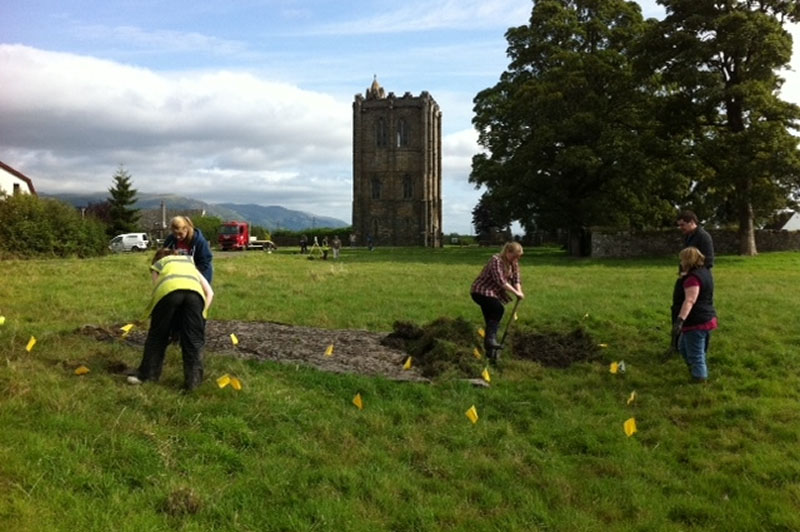 Volunteers breaking ground in the shadow of the abbey tower