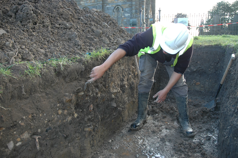 Cleaning up a trench near the abbey tower